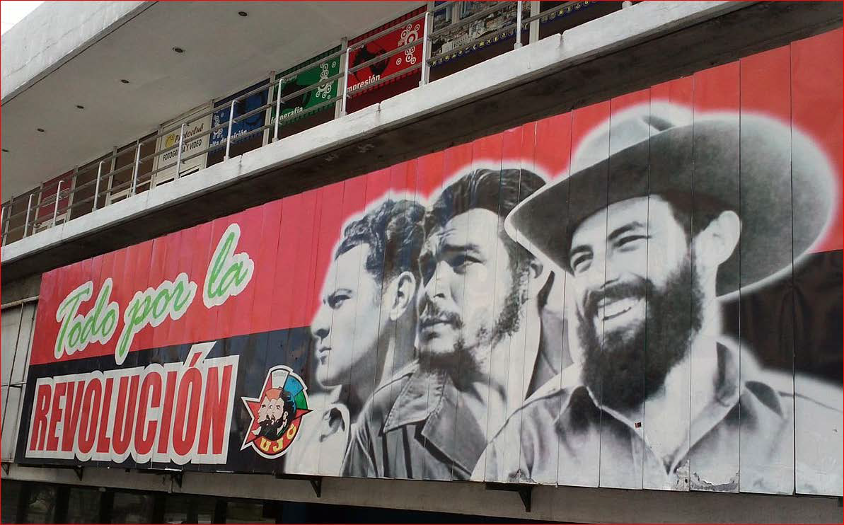 A poster on the side of a building with the faces of three key people from the Cuban Revolution.