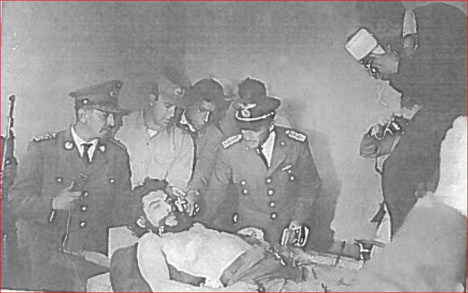 A black and white photograph of Che Guevara surrounded by several men who are dressed in military uniforms.